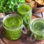 Glass jars of cilantro pesto on wood cutting board