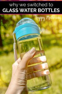 Hand holding a glass water bottle in front of greenery