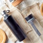 Glass and stainless steel water bottles with other eco-friendly items on a table
