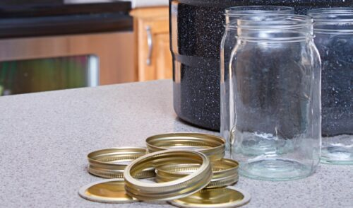 Canning jars, lids and water bath pot on a kitchen counter