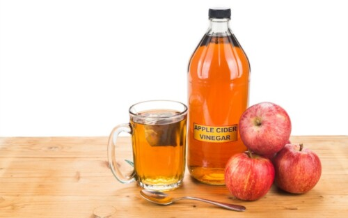 Apple Cider Vinegar on a table with apples and a tea cup