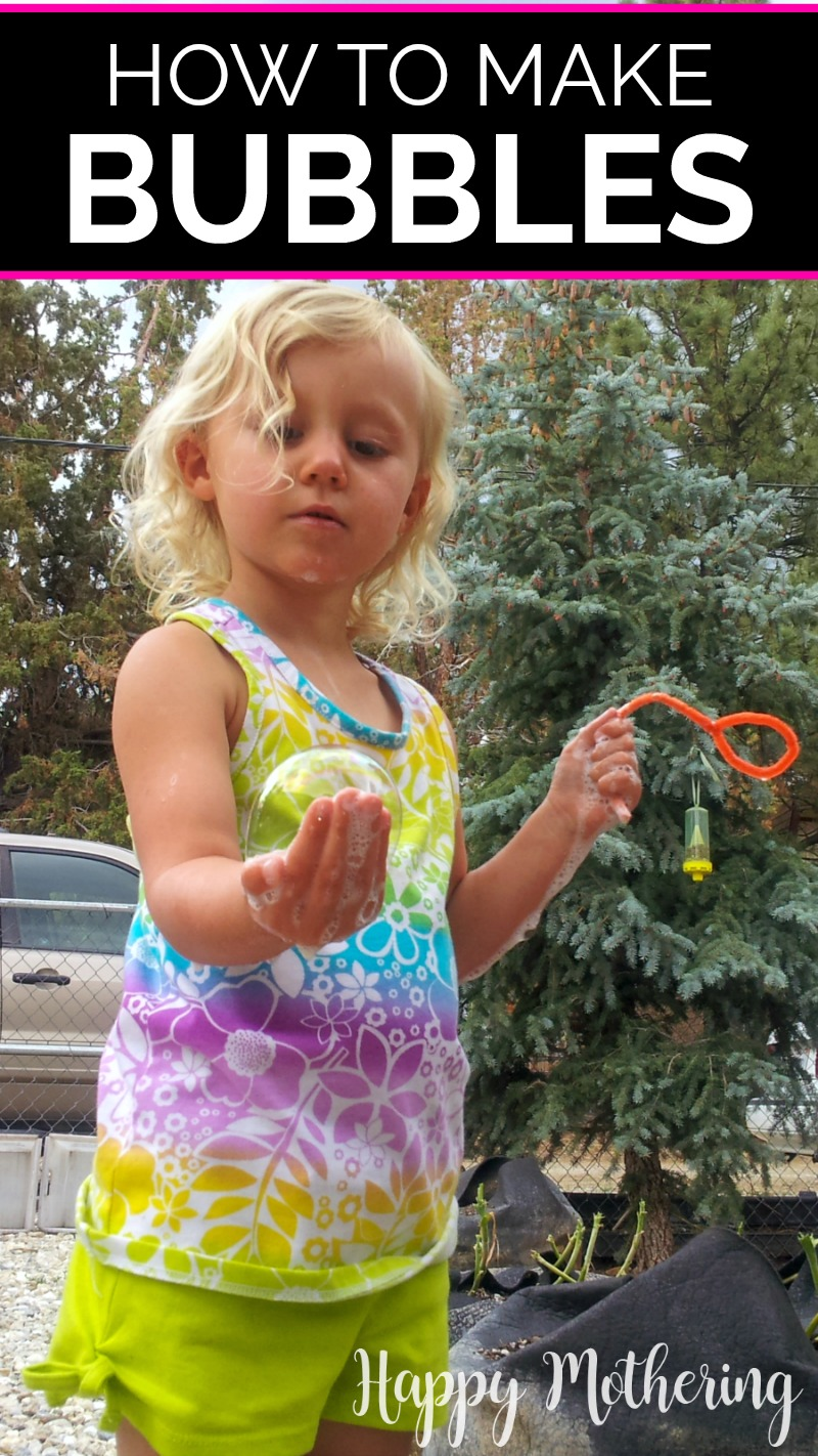 Kaylee carefully holding a bubble she blew with her homemade bubbles with a pipe cleaner wand in the other hand