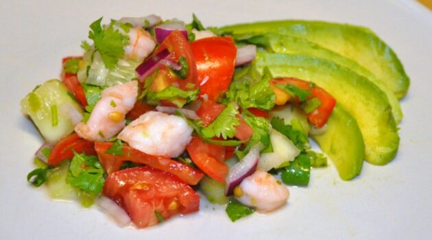 Shrimp ceviche with avocado slices on a white plate