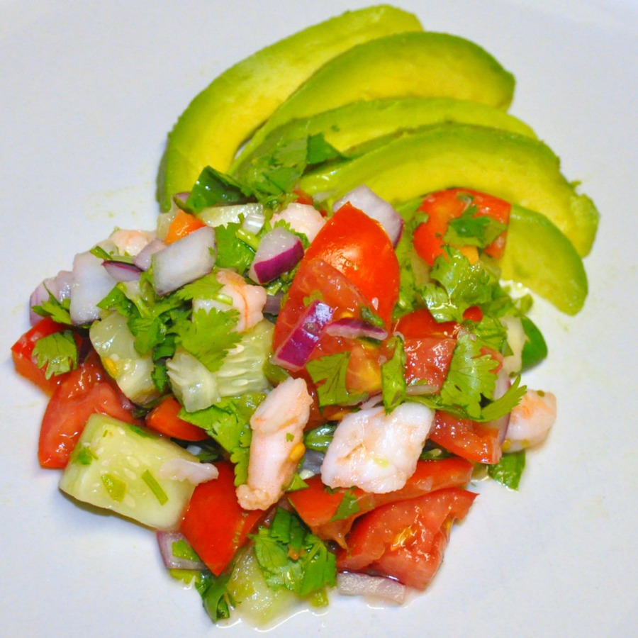 Overhead view of shrimp ceviche with avocado slices on white dinner plate