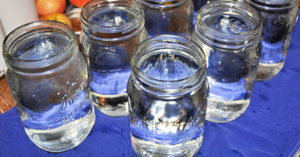 Quart sized mason jars filled with hot water on towel on kitchen counter.