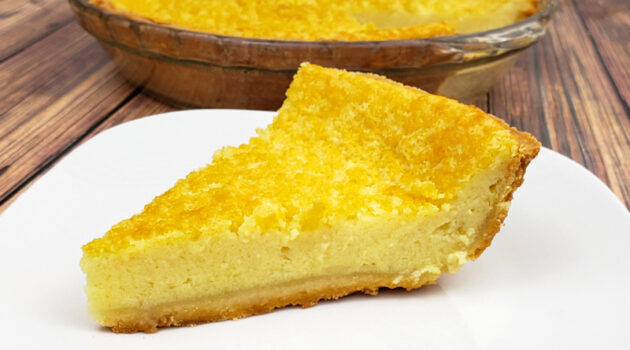 Close up of slice of homemade gluten free buttermilk pie on white dessert plate next to pie pan on wood table.