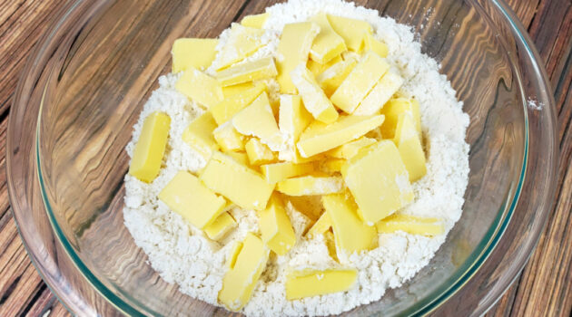 Chopped up butter in glass mixing bowl with flour, sugar and salt combo.