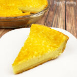 Gluten free buttermilk pie slice on square white plate on wood table next to pie plate.
