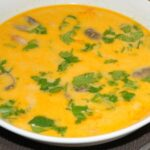 Close up of Thai Coconut aka Tom Kha soup in a white bowl