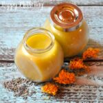 Close up of glass jars of calendula lavender salve on weathered blue wood table with dried flowers