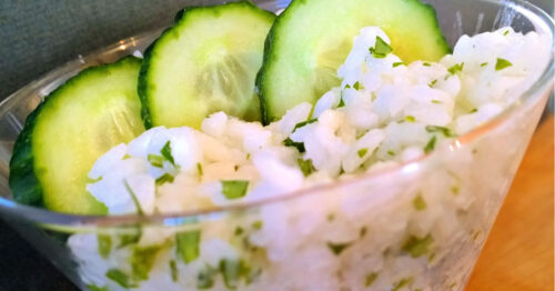 Close up of cilantro lime rice garnished with cucumber slices.