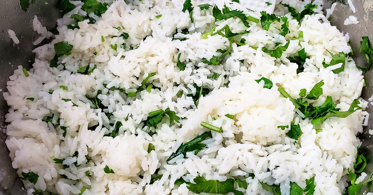 Chopped cilantro being stirred into the lime rice.