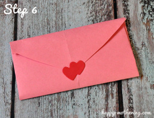 Pink construction paper envelope that folds out into a heart when opened