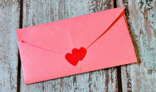 Pink construction paper envelope sealed with heart stickers