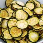 Close up of white bowl full of homemade zucchini chips on a blue painted wood table