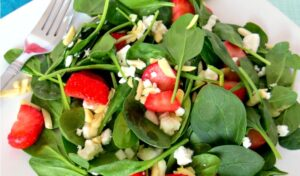 Close up of strawberry spinach salad on white plate with silver fork