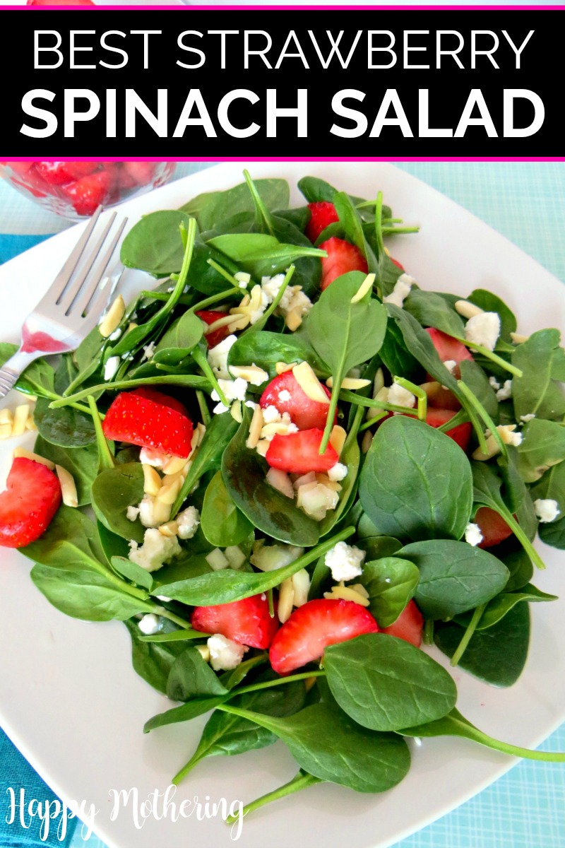 Strawberry spinach salad served on a square white plate with a silver colored fork with a bowl of strawberries in the background