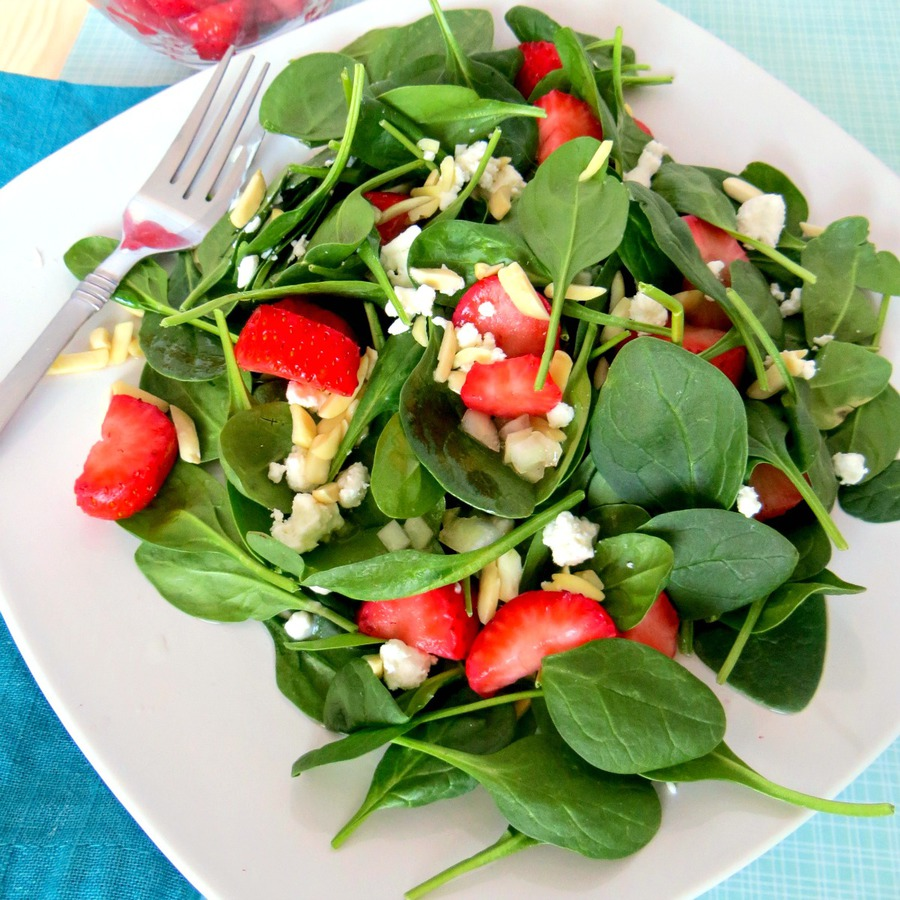 Square white plate of strawberry spinach salad topped with nuts and feta with a fork on the plate