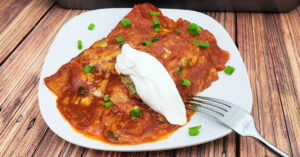Chicken enchiladas topped with sour cream and green onions.