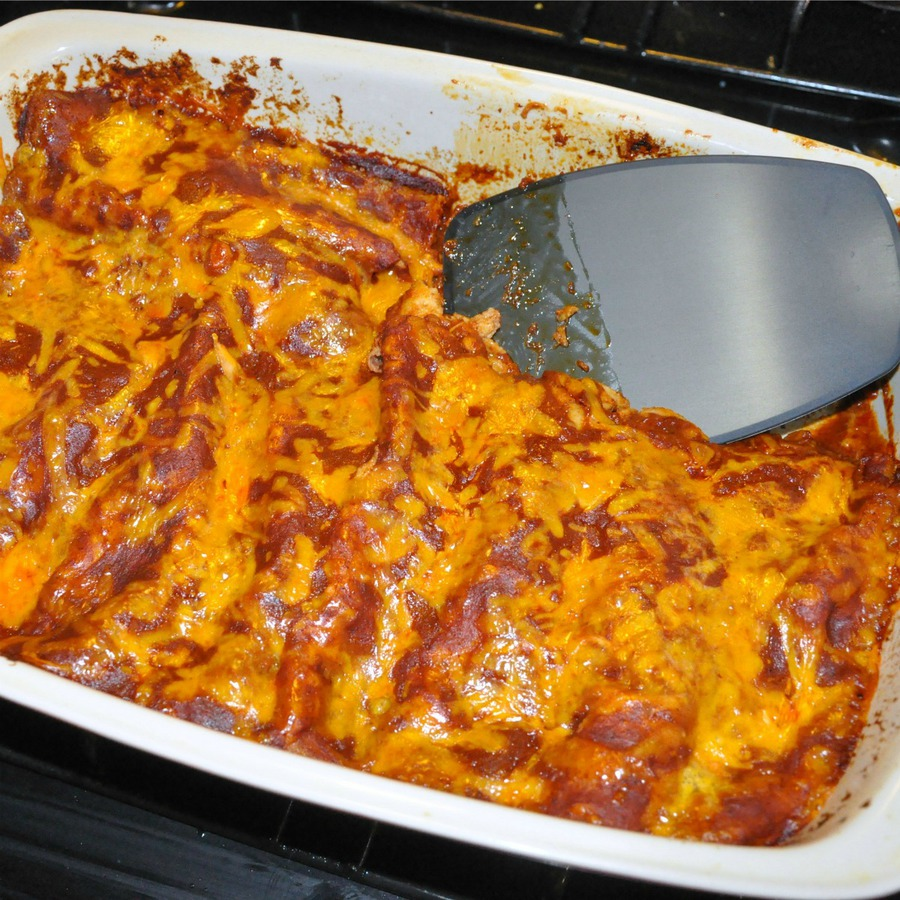 Homemade chicken enchiladas in a ceramic casserole pan with spatula