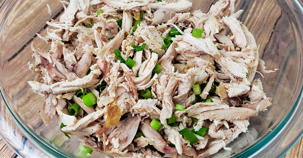 Shredded chicken and sliced green onions in clear mixing bowl.