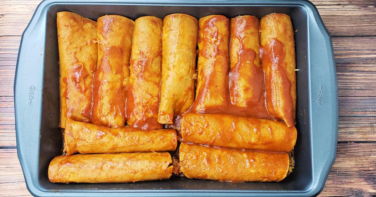 Baking dish filled with 12 enchiladas.