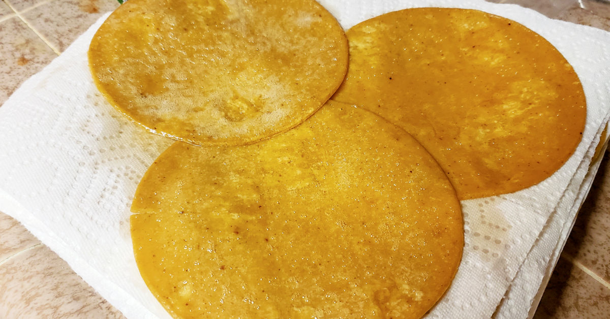 Lightly fried corn tortillas draining on paper towel lined plate.