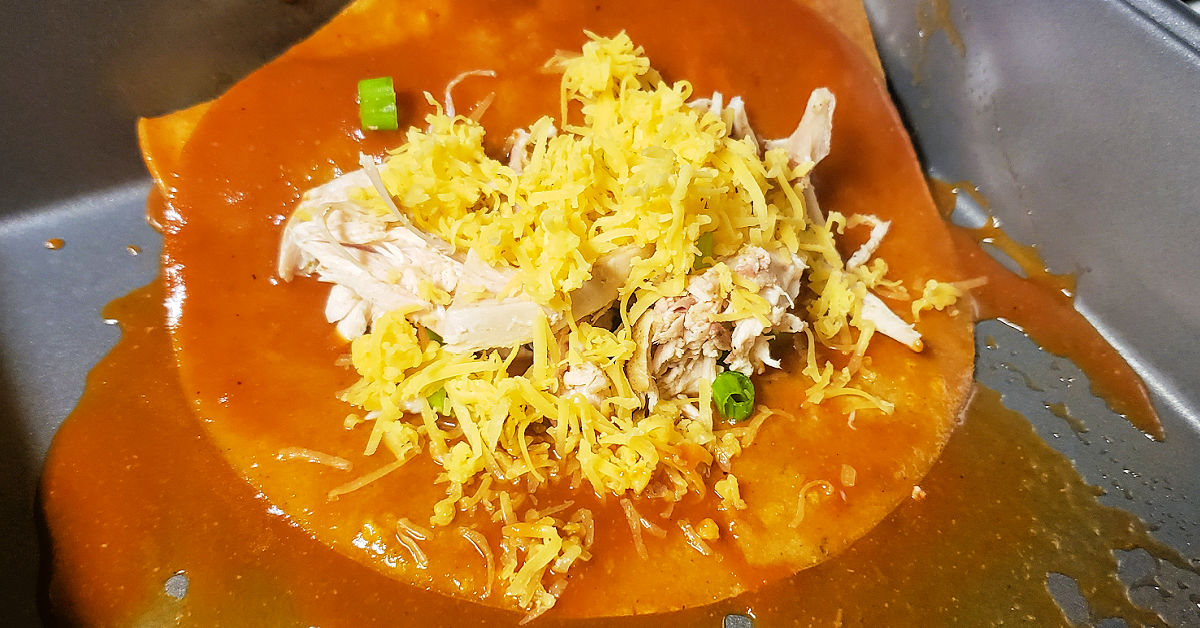 Chicken mixture and shredded cheese in center of corn tortilla dipped in enchilada sauce.