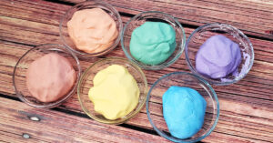 Cloud dough being colored with mica powder in small glass bowls.