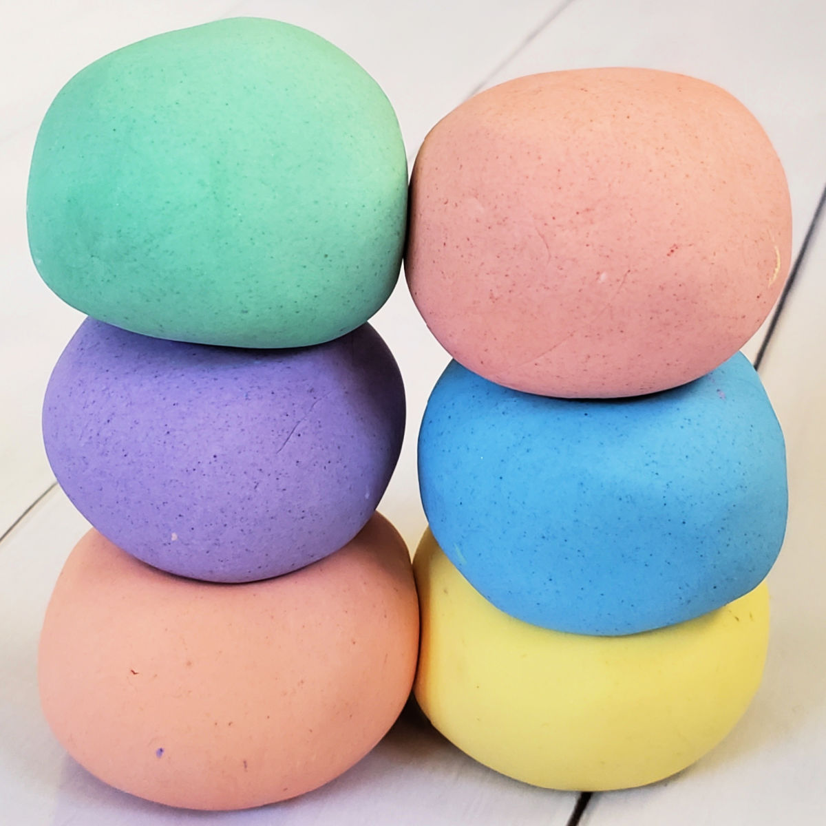 Close up of 6 balls in homemade cloud dough in rainbow colors.