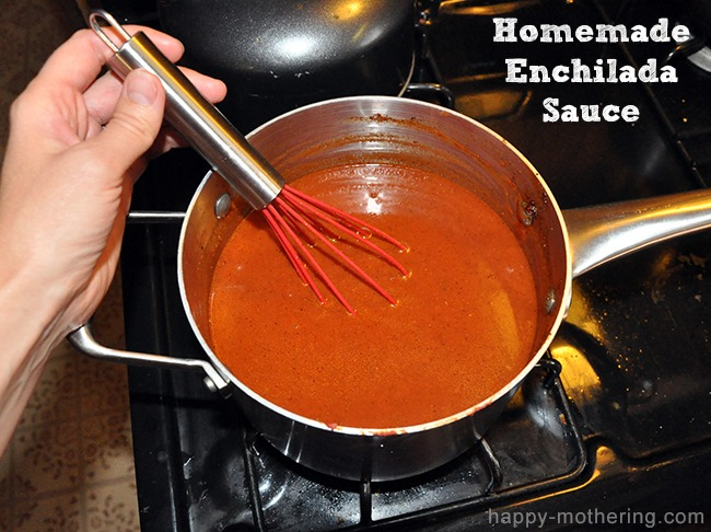 Homemade enchilada sauce simmering in a sauce pan while being whisked