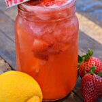 Strawberry lemonade in quart sized mason jar with red lid and straw on wood picnic table with one lemon and two strawberries