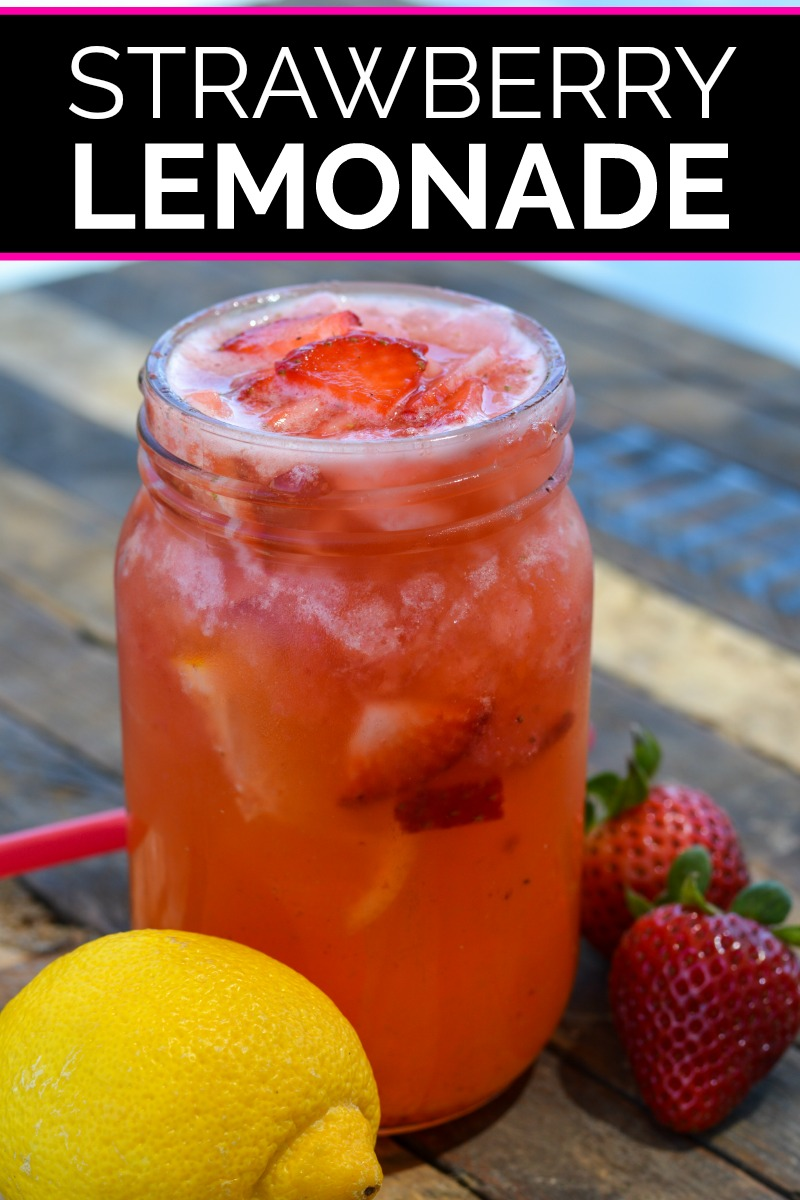 Strawberry lemonade served in quart sized mason jar on wood picnic table with red straw, two whole strawberries and a lemon