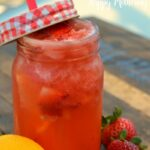 Quart sized mason jar with red lid and straw, filled with homemade strawberry lemonade on wood table next to whole lemon and two strawberries