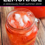 Overhead view of cup of ice cold strawberry lemonade with full pitcher behind it on table