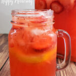 Pint sized mason jar with handle filled with strawberry lemonade with pitcher in background on wood table