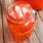 Strawberry lemonade in quart sized mason jar on wood table with red straw and lid, lemon and strawberries