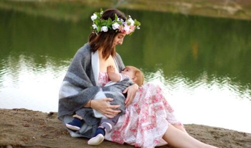 Brunette mom with flower crown breastfeeding baby while sitting by a lake