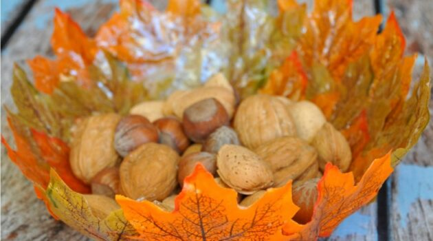 Fall leaves bowl with nuts in it on a blue wood table