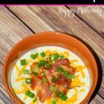 Faraway view of bowl of leftover baked potato soup with bacon, cheddar and chive toppings