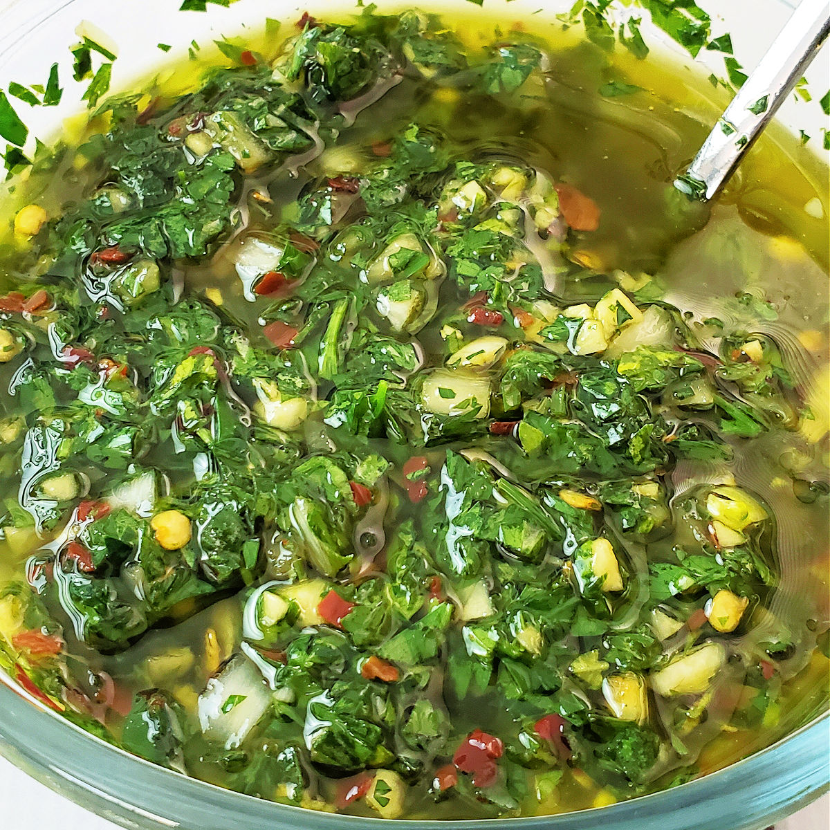 Overhead view of pint sized mason jar with a spoon dipped into the Chimichurri sauce