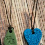 Green and blue polymer clay necklaces on a wood table