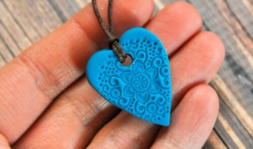 Blue heart shaped essential oil diffuser pendant in a hand