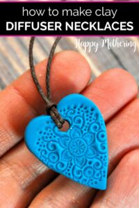 Blue heart clay essential oil diffuser necklace in a hand