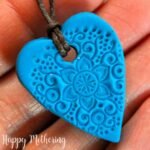 Close up of homemade polymer clay essential oil diffuser necklace