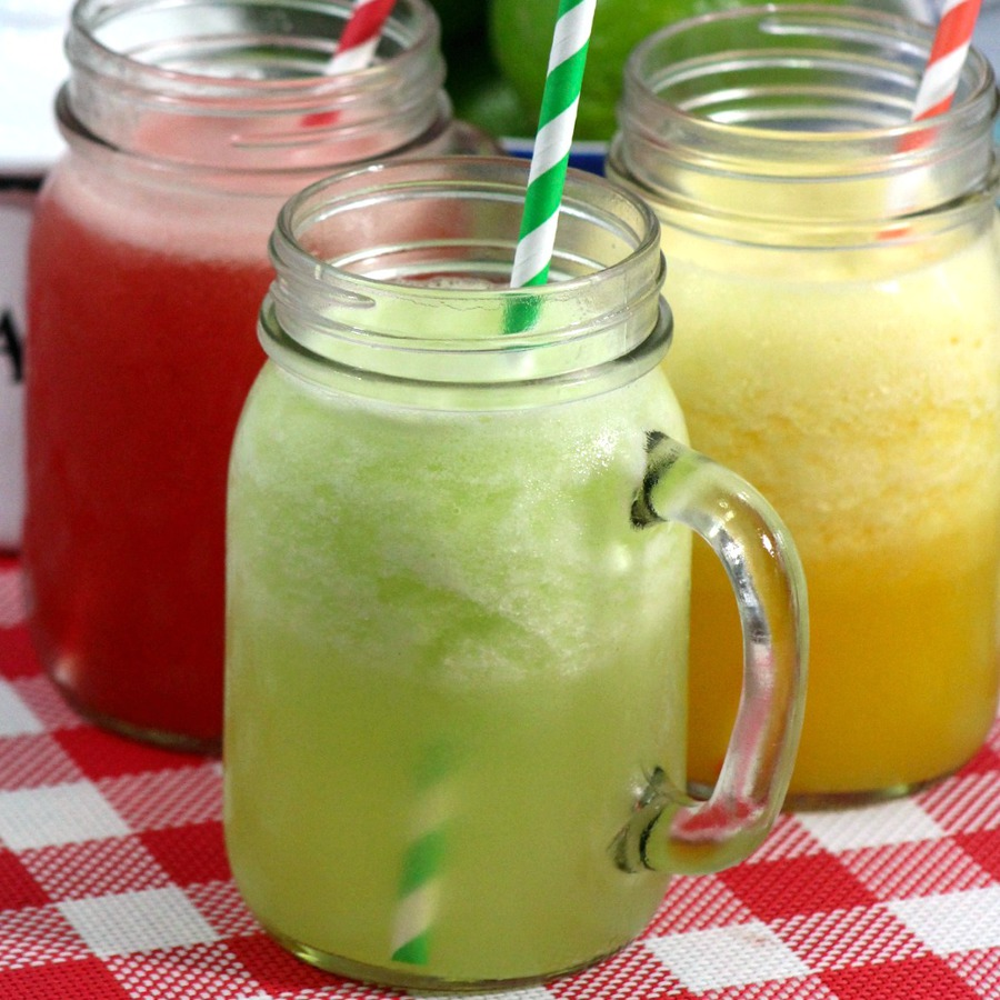 Close up of glass jars with handles of watermelon, cucumber and orange agua fresca served with paper straws