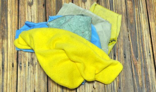 Yellow, blue and green microfiber cloths on a wood table