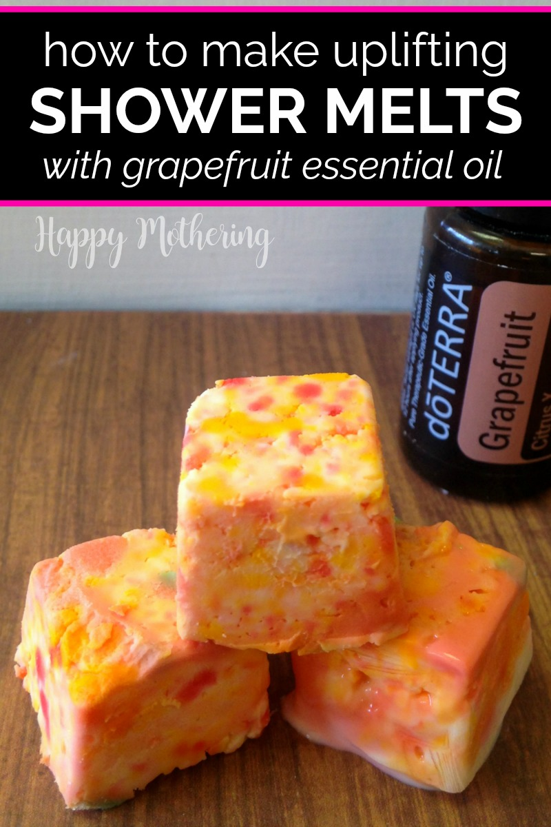 Three grapefruit essential oil shower melts on a table with a bottle of essential oil