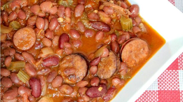 Slow cooker sausage, red beans and rice in a white bowl on a checkered tablecloth
