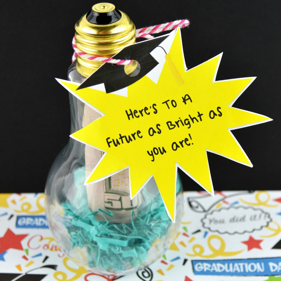 "Square image of clear plastic craft light bulb stuffed with blue shredded paper and $50 US bill and labeled with printable tag that reads, ""here's to a futures that's as bright as you are"""